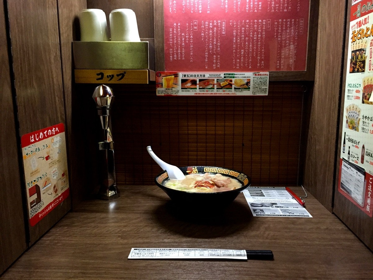 A small cubicle with a single bowl of ramen on it